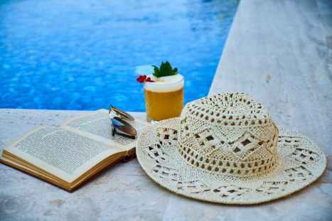 beige straw hat book sunglasses and drink beside pool